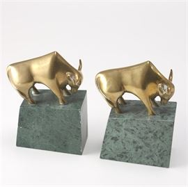 Pair of Brass Bull Bookends With Marble Bases: A set of brass bull bookends. This set of bookends features a brass bull on top of a green marble base. There are no markings.