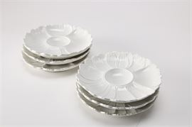 Round White Floral Ceramic Plates: A selection of six round white floral plates. Each plate has a scalloped edge in the shape of petals and a raised center. The bottoms are marked Italy.