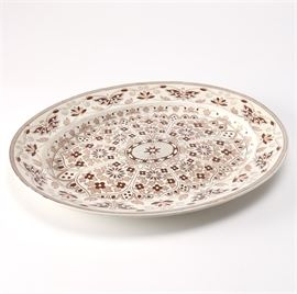 """Booths Indian Ornament Oval Tray: A Thomas Booth & Son Indian Ornament oval tray. This ceramic plate features a floral medallion surrounded by a field of tan and brown floral and foliage patterns with an arrow patterned rim. The underside features the markings, """"Indian Ornament T.B. & S."""""""