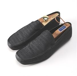 """Dolce & Gabbana Loafers: A pair of Dolce & Gabbana loafers. The black slip on shoes feature """"Dolce & Gabbana"""" printed across the material of the loafers with leather lining. Accompanying the loafers is a Dolce & Gabbana dust cover. The loafers are size 9.5."""