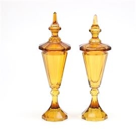 Pair of Brown Glass Decanters: A pair of brown glass decanters. The decanters have a flame style finial on a rounded glass lid with panels and an overhanging edge. Other features include a fluted shaped body with panels, a flared stem that flows into the base with a hexagonal design and a rounded base.