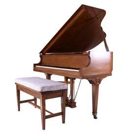 Lindeman and Sons Grand Piano and Bench: A Lindeman and Sons grand piano and bench. The piano is constructed of wood and wood veneer and finished in chestnut stain. The fall board bears Lindeman & Sons Est.1836 label. The piano is supported by three square tapered legs on caster wheels with brass pedals. The matching bench is upholstered in black and white music note printed fabric.