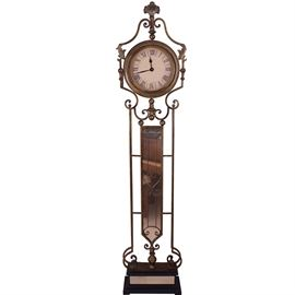 Contemporary Grandfather Clock: A contemporary grandfather clock. The clock features a heraldic shell finial atop a flat dial framed in a bronze tone metal with rope detailing. The face of the clock is connected to the scroll designed metal body over a rectangular, vertical gold tone mirror and hammered metal base. The clock rises on a black pedestal base with mirrored accents. The clock is battery powered.