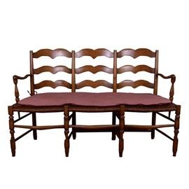 French Rush Seat Bench: A French rush seat bench mimicking a trio of chairs. The bench seats three and is complete with a scalloped back and curved arms on either side, woven rush seats, supported by turned legs. The bench also includes a cream and red checkered cushion.