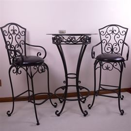 Contemporary Wrought Iron High-Top Table and Chairs: A contemporary wrought iron finished high-top table and chairs. This chic cafe style set includes a round, overhung glass top table with black wrought iron base with scrolled details, circular footrest and cabriole style legs with disc feet. The pair of chairs have scrolled backs, arms and matching cabriole legs with disc feet and are upholstered with padded black vinyl seats.