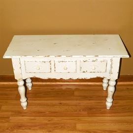 Distressed Accent Table: A distressed accent table. This quaint table is rectangular with an overhung top with painted white and intentionally distressed finish.The table is complete with three drawers, scalloped apron, and supported by turned legs.