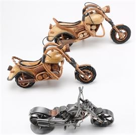 Group of Carved Wooden and Soldered Metal Motorcycles: A group of carved wood and soldered metal motorcycles. Two of these motorcycles are made of carved natural wood and twisted branches with black woven reeds serving as accents. The metal motorcycle has a steel construction with copper accents and a rounded base on the back wheel.