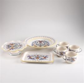 """Ceramic Deruta Tableware: A set of ceramic Deruta tableware. This selection includes one rectangular platter, one footed cake stand, one larger serving bowl, and four mugs. These pieces feature matching patterns depicting multicolored fleur-de-lis style designs to the center with scrolls, flowers, and yellow trim. The underside of each is stamped """"Deruta Ceramiche, Made in Italy""""."""