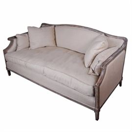 Restoration Hardware Louis XVI Style Settee: A Restoration Hardware Louis XVI style settee. This piece has exposed wood detail in a rustic finish, with taupe linen-like upholstery. The back is slightly arched with wood framing the back and sides, and scrolling under to form hand rests. The piece stands on tapered feet and includes matching throw pillows. For coordinating pieces, see item 17BAL032-057.