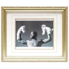 "Ursula Coyote Signed Limited Edition Gelatin Silver Print ""Pump"": A signed limited edition gelatin silver print titled Pump by Santa Fe photographer Ursula Coyote. This print is edition number 1 of 10 and was produced in 2002. Depicted is a robust man holding up two poodles as if they were weights. It is doubled matted in a beige matte and an off-white matte with a single v-groove. It is framed in an ornate gold tone wood composite moulding. The signature is located on the photographic paper on the lower right hand side. Ursula Coyote is a photographer active in Santa Fe, NM and is known for her current break out movie stills on set of renowned shows such as Breaking Bad and Orange is the New Black ."