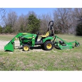 John Deere Tractor 200CX Loader/ Tractor 2305HST: A John Deere Tractor 200CX loader/ tractor 2305HST. This John Deere Tractor comes with a front loader and a rotary cutter attachments. This tractor, loader, and rotary cutter are green in color with the John Deere yellow accents.