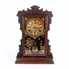 """Antique Seth Thomas German Gingerbread Style Mantel Clock: An antique Seth Thomas German gingerbread style mantel clock. The mantel clock is in a dark finish and marked """"Thomas Clock"""" inside. The clock features a decorative pendulum, a glass door with gold tone floral motif, and roman numerals on clock face."""