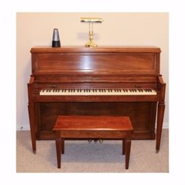 Baldwin Piano with Stool: A Baldwin Piano with Stool. The wood on the piano has a medium tone finish. Included are a matching stool which opens for storage, a metronome, and a gold tone lamp.