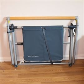 Fluidity Exercise Evolved Portable Ballet/Pilates/Yoga Barre: A Fluidity exerciser Evolved portable ballet/pilates/yoga Barre. The barre opens to reveal a pull out rectangular mat. The support bar is a light wood.