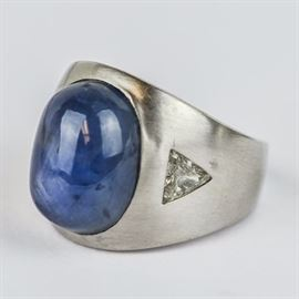 Men's 18K White Gold, Star Sapphire, and 1.00 CTW Diamond Ring: A men's 18K white gold ring featuring one center star sapphire oval cabochon flanked by flush set trillion cut diamond side stones with a total approximate carat weight of 1.00 ctw.