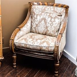 Vintage Upholstered Armchair: A vintage upholstered armchair. This chair features carving throughout the exposed wood frame including foliate detail to the top rail and reeded front supports. It has a brocade pattern upholstery to the interior and exterior and includes a back pillow.