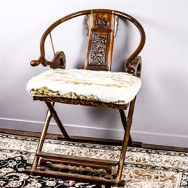 Chinese Carved Wood Folding Chair: A Chinese folding chair. Features a wooden construction with a carved back splat, a horseshoe top rail, and brass detail. Includes a detachable, faux fur foam seat cushion.