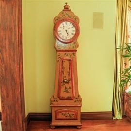 Reproduction Swedish Grandfather Clock: A reproduction Swedish grandfather clock. This clock features a painted wood construction decorated with birds and vining throughout. It has a distressed face with black roman numerals. Labeled by Woodland Furniture and Timeworks. Item is untested.