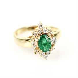 14K Yellow Gold, Emerald, and Diamond Ring: A 14K yellow gold ring featuring one faceted oval emerald flanked by marquise cut diamond side stones and a border of round brilliant cut diamonds.
