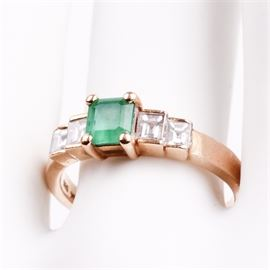 14K Yellow Gold, Emerald, and Diamond Ring: A 14K yellow gold ring featuring one rectangular emerald flanked by square cut diamond side stones.