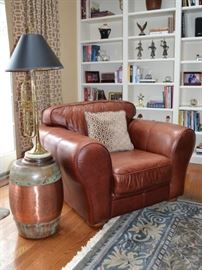 Leather club chair, copper garden stool and trumpet lamp