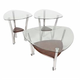 Glass Top Occasional Tables: A set of glass top occasional tables. This three piece set includes a coffee table on casters and two smaller side tables. Each table features a tempered glass triangle top, three chrome legs, and a lower wood shelf. The tables have manufacturing stickers on the bottom.