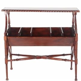 Mahogany Side Table: A mahogany side table. This wooden side table features a mahogany finish with a rectangular top decorated by carved, scalloped detailing along the sides. Beneath are four support rails, two turned style and two curved, connecting to a cradle base. Inside the base are four triangular dividers, each with geometric cut-out designs. A cross stretcher supports four spade legs.