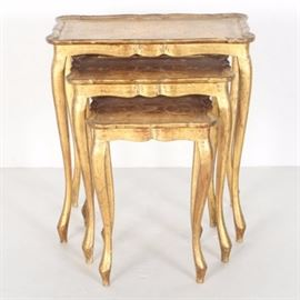 Three Nesting Tables: A grouping of three nesting tables. These nesting tables feature wooden construction with a brushed gold tone finish. The tops are scalloped and each fixed with a filigree detail. The legs are cabriole in style.