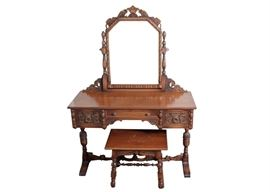 Antique Wooden Vanity and Stool: An antique wooden vanity and stool. This vanity and stool has intricate carvings. It has three drawers across the front of the vanity and a removable mirror at the back. The small stool has a matching design.