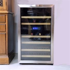 Danby Designer Wine Cooler: A Danby Designer electric wine cooler with digital display. The model DWC283BLS, serial number 0907100102007 was made in 2007. It is black with a brushed nickle front, single glass door and six removable wooden racks inside.