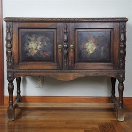 Hand Painted Antique Mahogany Server: A small mahogany Eastlake buffet cabinet or server with a floral still life, hand painted on each door panel. Additional features include ornate pilaster columns at the center of the two doors and at the corners, detailed fancy molding, applied acanthus leaf accents, a short scalloped skirt and a wide H-stretcher base.