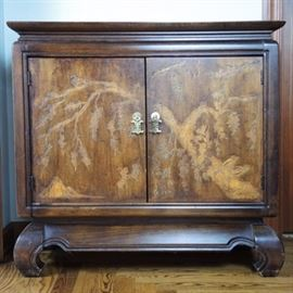 Asian Style Buffet Cabinet: A contemporary Asian style buffet server. This small cabinet is constructed of wood in a walnut stain with a flowering tree pattern embossed on the doors. Oriental brass pulls open the double doors. Piece sits on traditional, short curved C-scroll or 'opium legs'.