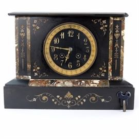 Antique Black Marble Stone Inlay Mantel Clock: An antique flat-top black marble mantel clock with multicolored stone inlay. This weighty clock features a black dial with gold-tone Arabic numerals, embossed brass-tone chapter ring, hinged glass door, two key holes with brass rings and incised gilt decoration. The works are numbered A.1 7812; brass pendulum marked R A 2487. Base is open. Includes key.