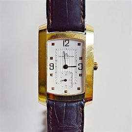 """Baume & Mercier 18K Gold """"Hampton"""" Wristwatch: An 18K yellow gold Baume & Mercier Hampton quartz wristwatch on an alligator leather strap with stainless steel gold plated deployment buckle."""