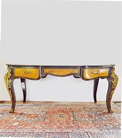 Early 20th Century Louis XV Style Bureau Plat: An antique Louis XV style bureau plat, early 20th century. This fabulous desk enjoys a leather-inlaid top set in a cross-grained mahogany and finished to the edge with fleur ormolu banding and scroll and fleur corners. The mahogany scalloped apron is outfitted with three cross-grained satinwood drawers outlined in ormolu trim and embellished with ornate polished brass pulls. The desk's cabriole legs are lavishly dressed in ormolu corner sleeves with scrolling foliate feet. The back of the desk is designed in a complementary fashion, albeit without the working drawers.