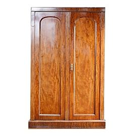 Antique Mahogany Armoire: An antique mahogany armoire. The armoire is designed with a straight top cornice and side pilasters, with two paneled arched top doors, flat panel sides, and a beveled flat base. The right door has a polished brass pull, the doors opening to a brass hanging rod to the top, and pair of storage drawers to the base.