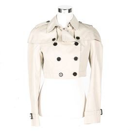 Women's Burberry Trench Style Jacket: A women's Burberry trench-style jacket. This USA size 6 jacket has a double row of buttons in front, a buttoned , fitted cape, and belted sleeves. Made of cotton on the exterior and 60% acetate/40% cupro interior, it is lined in plaid, marked, and comes with original tags and extra buttons.