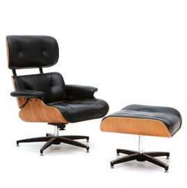 Eames Style Chair with Footstool: An Eames style chair with matching footstool. Upholstered in black leather. The frame has a rosewood veneer and metal hardware. The base of both the chair and footstool are X-shaped, in chromed metal with disc feet. The chair rotates and reclines. No maker's name.