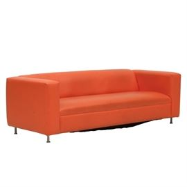 Mid Century Modern Orange Sofa: A Mid-Century Modern bright orange vinyl upholstered sofa. Offering clean tailored aesthetics with a low square profile and fixed seat and back cushion, raised on chrome legs. Coordination sofa is located at 506 in this sale.