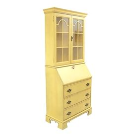 """Vintage Jasper Cabinet Yellow Wooden Secretary: A vintage yellow wooden secretary by Jasper Cabinets. This piece features two cabinet doors along the top and interior cabinet shelving. The lower portion of the piece has a slant front desk that, when opened, has a variety of organizational cubbies and a drawer. Below the desk are three drawers with dovetail construction. The interior of one of the drawers is marked """"Jasper Cabinets"""" along the side. The entire secretary stands on bracket feet below."""