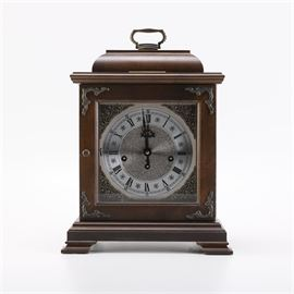 Hamilton Wheatland Chiming Mantel Clock: A Hamilton Wheatland chiming mantel clock. This dark brown wooden clock features a round clock face with black hands and black Roman and Arabic numerals. The face of the clock is housed behind a door with silver tone details. The clock comes with a winding key.