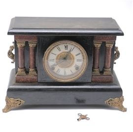 Neoclassical Style Mantel Clock: A Neoclassical style mantel clock. This clock features a black painted finish to its wood and resin frame with gold-tone accents. The clock rests on four gold-tone ornamental legs. The body of the clock is ornamented with a pair of Corinthian columns on either side of the dial. The white dial features Arabic hour indicators in gold-tone casing. Includes key for winding. This clock was tested and found not to be in functioning condition.