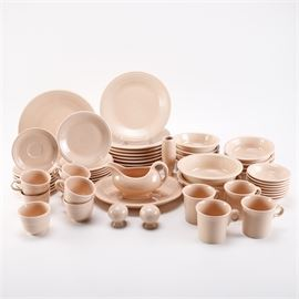 """Pink Fiesta Tableware: A large set of pink Fiesta tableware. This collection includes one round serving plate, eight dinner plates, two serving bowls, eight salad plates, eight cereal bowls, eight saucers, eight fruit bowls, one oval platter, one gravy boat, seven footed cups, four mugs, one bud vase, and a salt and pepper shaker set. These pieces all feature pale pink exteriors with concentric circle designs and glazed finishes. The underside of each is marked """"Fiesta, USA."""""""