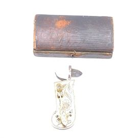 """Antique Bloodletting Instrument with Case: An antique blood letting instrument with case. This piece features a triangular-shaped blade in a brass case stamped with a floral motif. The instrument comes in a hinged box stamped """"G.B."""" with a beehive on the top."""