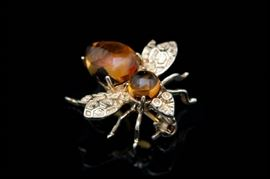 14K Yellow Gold and Citrine Wasp Pin: A 14K yellow gold and citrine wasp pin. The wasp pin features a citrine head and body with wings impressed with a honeycomb pattern.