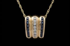 """14K Gold, Blue Sapphire and Diamond Slide Pendant with Chain: A 14K gold, blue sapphire and diamond slide pendant with chain. The wedge-shaped slide measures approximately 0.45"""" x 0.55"""" and features seven channel-set diamonds flanked by two rows of channel-set blue sapphires. Included is an 18"""" 14K yellow gold cable chain"""