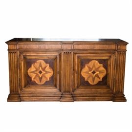 "Ethan Allen ""Lombardy"" Marquetry Sideboard: A ""Lombardy"" marquetry sideboard by Ethan Allen. This stately piece is crafted from gmelina wood and has three fluted pilasters to the front. The cabinet has two shallow drawers over two paneled doors embellished with quatrefoil veneering and aged brass hardware. The sideboard's interior has two adjustable shelves."