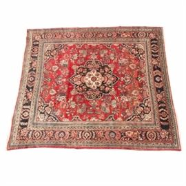 Hand Woven Persian Khoye Style Area Rug: A hand woven Persian Kohye style area rug. The rug features a central medallion in a palette of red, rose, blue, navy and cream on a warm red field accented with corner spandrels. The rug has a wide outer band in a complimentary palette with a one-inch fringe to either end.