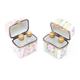Pair of Limoges Perfume Boxes with Empty Perfume Bottles: A pair of Limoges perfume boxes with empty perfume bottles. These hand-painted pieces feature floral patterns in a variety of colors. The interior edges of the boxes are lined in a gold-tone metal trim with one clasp shaped like a rose and the other shaped like a bow. The bottles are a clear glass with brass lids that double as the perfume droppers. There are maker's marks on the bottom of both boxes.