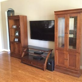 Open lighted wall unit with three glass shelves and storage cabinet underneath,  lighted wall unit/china cabinet with mirrored back, glass doors and glass shelves with storage cabinet underneath, and an entertainment center with wrap-around doors and speaker enclosure.